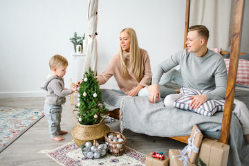 Cute baby boy decorating christmas tree with parents