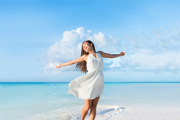 Wall Mural - Freedom young woman carefree and happy with open arms on blue ocean landscape beach background. Asian girl in white dress feeling happiness enjoying her travel vacation.