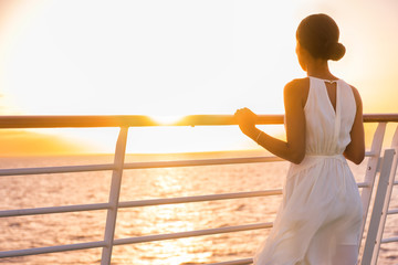 Wall Mural - Cruise ship vacation woman enjoying sunset on travel at sea. Elegant happy woman in white dress looking at ocean relaxing on luxury cruise liner boat.