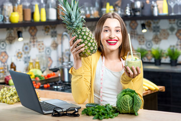 Young woman drinking green smoothie on the kitchen table with laptop, fruits and vegetables. Healthy eating concept