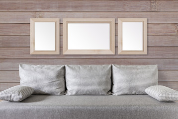 Three blank photo frames on wooden panels wall, over modern couch, rustic style interior decor mock up