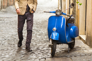 Fotobehang Scooter uomo che si dirige verso uno scooter vintage a Roma