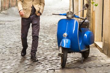 uomo che si dirige verso uno scooter vintage a Roma