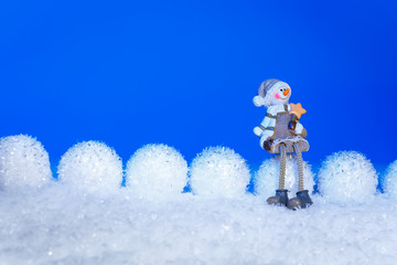 Xmas or new year composition with holiday decorations - snowballs lie in the line on snow and little man toy siting on  snowball on blue background. Christmas card