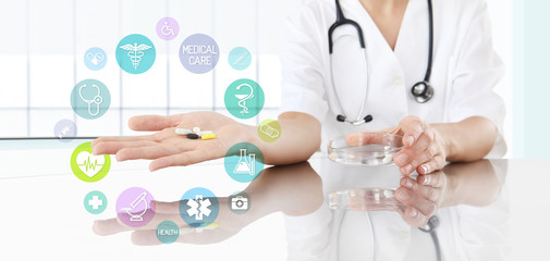 Doctor with pills in hand and colored icons. Health care and medical concept