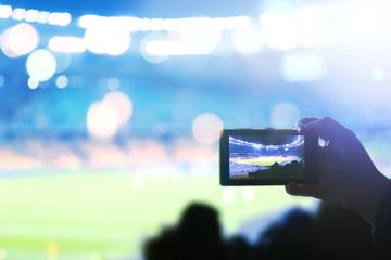 Woman taking photo of football stadium, closeup. Football stadium background
