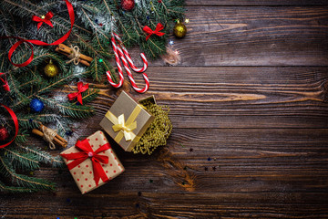 Christmas wooden background with snow fir tree. View with copy space.Christmas tree branch with decorations on wood background. Xmas holiday concept. Christmas gifts