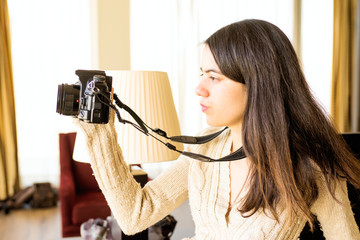 Young photographer manages his camera in a room