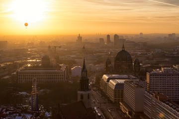 Beautiful panoramic aerial view over Berlin (Berlin Cathedral - Berliner Dom, City Palace - Stadtschloss, Potsdamer Platz, Bundestag - Reichstag) with romantic colorful sunset and balloon in the sky.