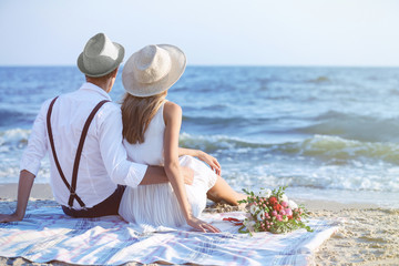 Young happy couple sitting back on beach