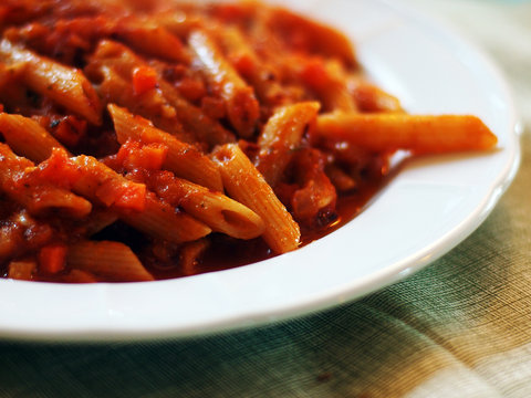 Italian food - Penne al'arrabbiata (Angry Pens), a classic italian pasta recipe with spicy tomato sauce, red hot peppers and parsley.