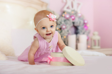 Little girl in a pink dress with  flower in her hair smiles and opens the box  gifts on  bed  the background of Christmas decorations