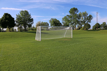 A view of a net on a vacant soccer pitch in morning light..