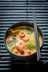 Enjoy your Tom Yum soup in black bowl with chopsticks