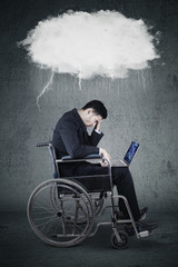 Disabled businessman with laptop and thundercloud