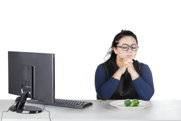 Fat woman prays before eats broccoli