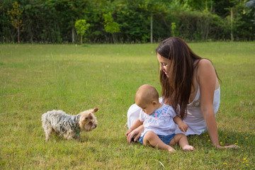 Happy mother and child with dog on grass in park