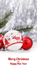 White and Red Christmas ornaments and fir tree branch on glitter bokeh background with space for text. Xmas and Happy New Year theme