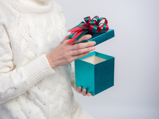 Celebrate the new year 2017.Close up shot of female hands holding a gift box and nice ribbon. Gift box color  in the hand of a woman wearing a knitted hat sweater on white  background.