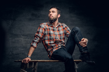 A bearded hipster male dressed in a jeans and a plaid shirt.