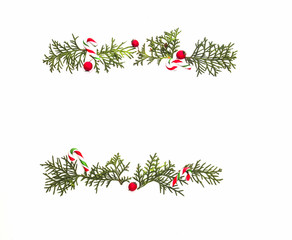 Christmas frame made of green thuja twigs and red wild rose fruits on white background. Top view, flat lay. Copy space for text