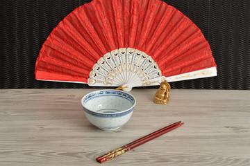 Chines bowl, chopsticks, a hand fan and a laughing Buddha