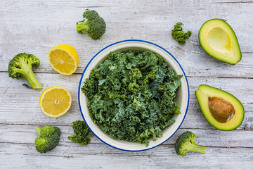 Fresh kale leaves and avocado on a wooden table.The raw ingredients for a salad.