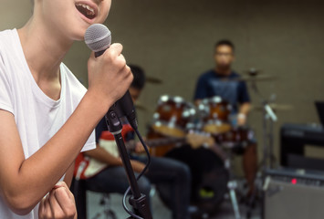 Closeup young Songer hand holding the microphone and singing on