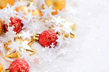 Christmas gold and red ornaments on the snow. Festive Christmas background