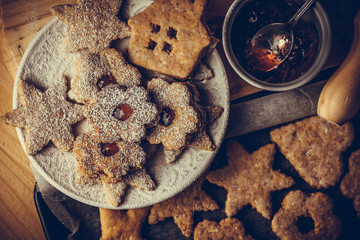 Homemade Christmas gingerbread and linzer cookies with jam, powdered, on baking sheet, top flat view, soft haze effect, vintage