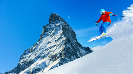 Man jumping from the rock, skiing on fresh powder snow with Matt