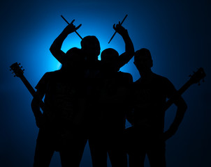 Band of young male musicians standing with instruments on a blue background