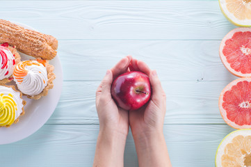 Hands of a young woman holding a red apple. Woman making a choice between sweets and fruits, made a choice in favor of fruits and holding an apple. Weight Loss. Unhealthy vs healthy food, top view.