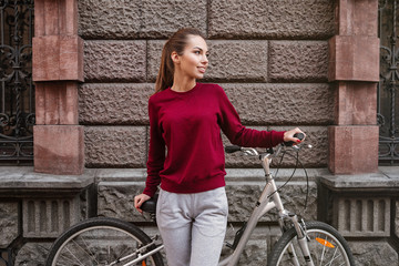 Woman dressed in sweater walking with her bicycle