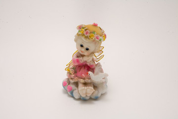 porcelain figurine angel girl in a pink dress with a pigeon isolated on white background