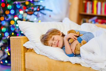 Little cute blond child sleeping under Christmas tree