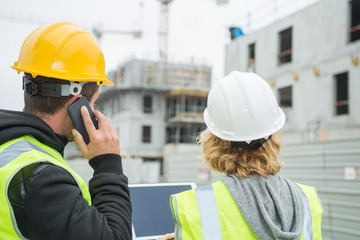 Two workers on a construction site using a tablet and a smartphone