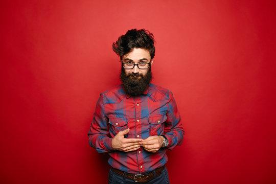 Single shy man with long beard on red