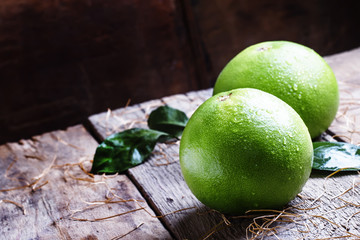Sweetie, green grapefruit or pomelo, vintage wooden background s