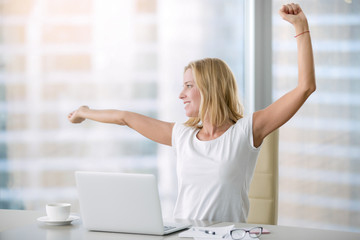 Young attractive woman at modern office desk, with laptop, stretching, getting a little exercise during the day, office workout, completing difficult task, time for lunch. Business concept