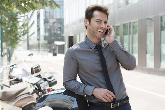 Businessman talking on cell phone in city, leaning against motor scooters