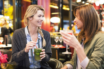 Women enjoying cocktail at bar