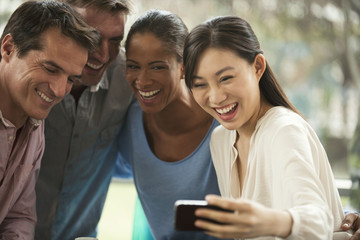 Group of happy friends taking selfie with a smart phone