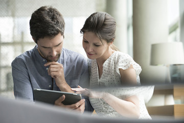 Couple using digital tablet together at home