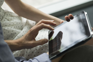 Couple using digital tablet, close-up