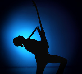 silhouette guitarists of a rock band with guitar on blue background