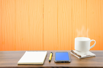 Hot coffee, smart phone, notebook and pen in wooden room