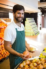 Male staff arranging fruits in organic section of supermarket