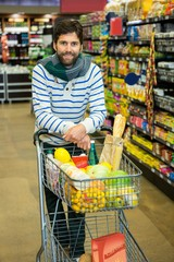 Portrait of smiling man with trolley in grocery section