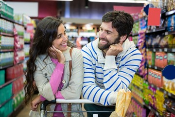 Couple leaning on trolley at supermarket